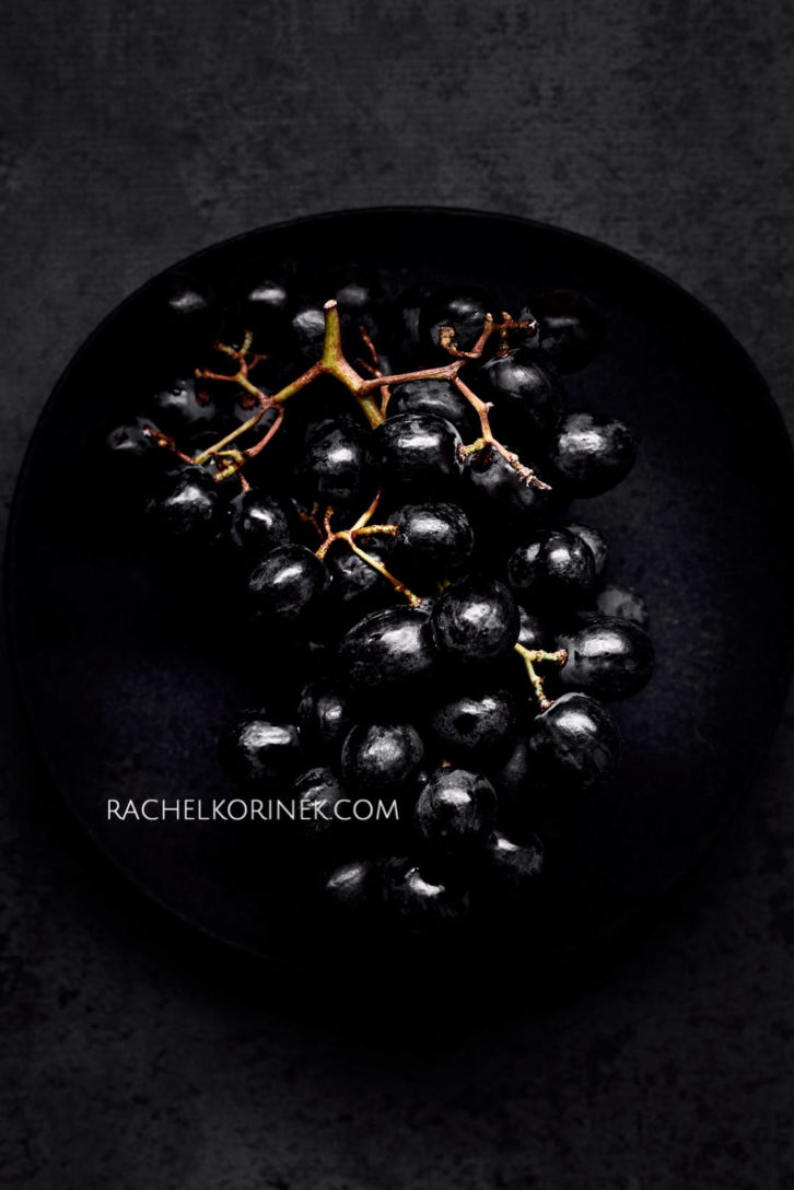 Dark black grapes sitting on a black plate. There isn't any colour to this photo so it appears black and white even thought it's real food!