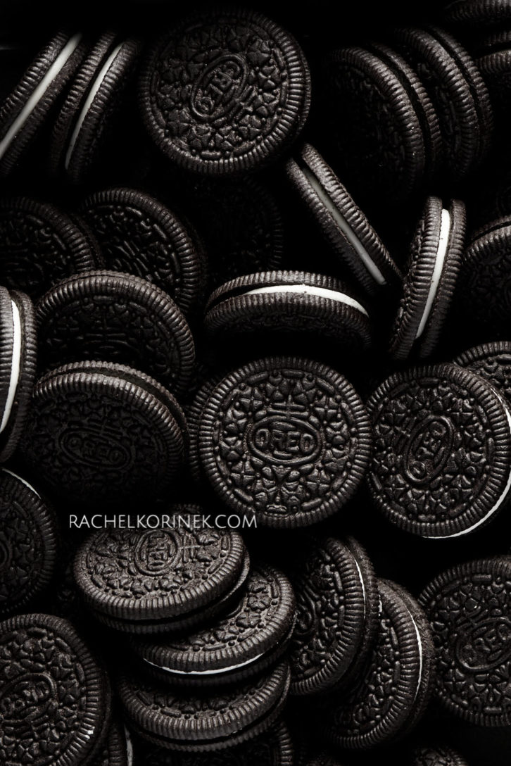 Lots of oreo cookies in dramatic lighting. There isn't any colour to this photo so it appears black and white even thought it's real food!