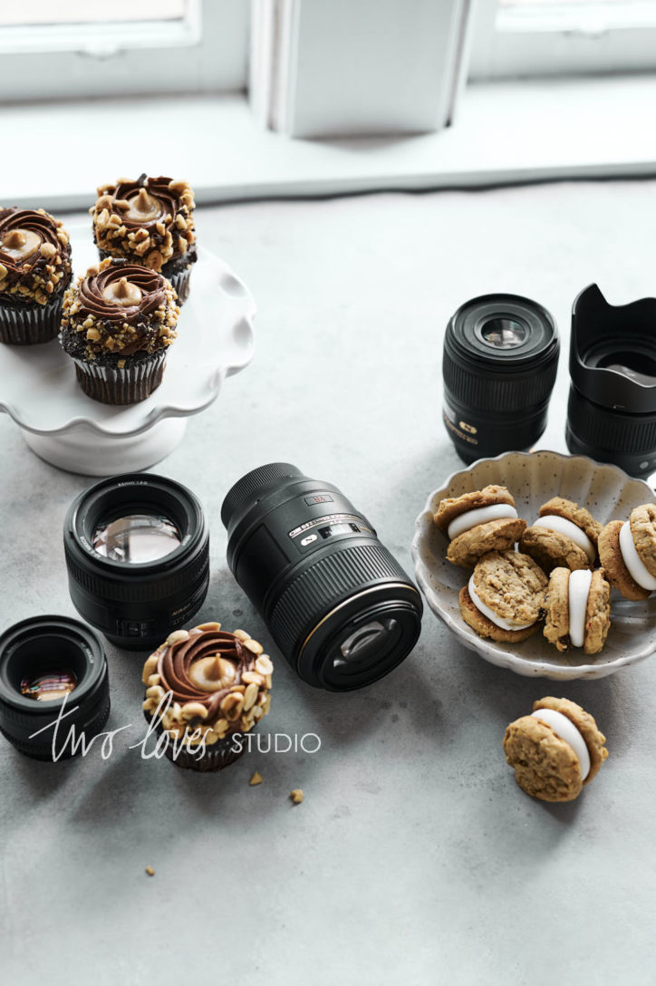Chocolate cupcakes on a cake stand and a bowl of cookies with five lenses.