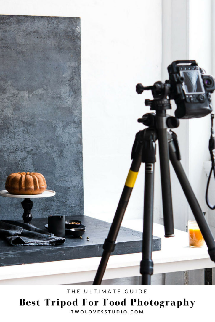 Behind the scenes food photography set up. Camera on tripod shooting a bundt cake on a cake stand on a dark grey background.