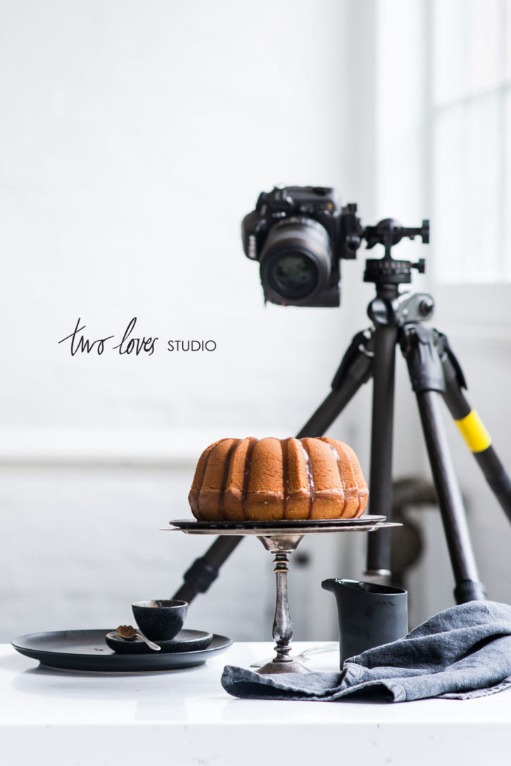 Camera on tripod shooting a bundt cake on a cake stand in a white studio. Behind the scenes food photography setup.