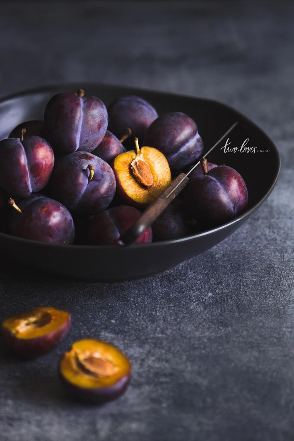 A bowl of plums with one cut in half.