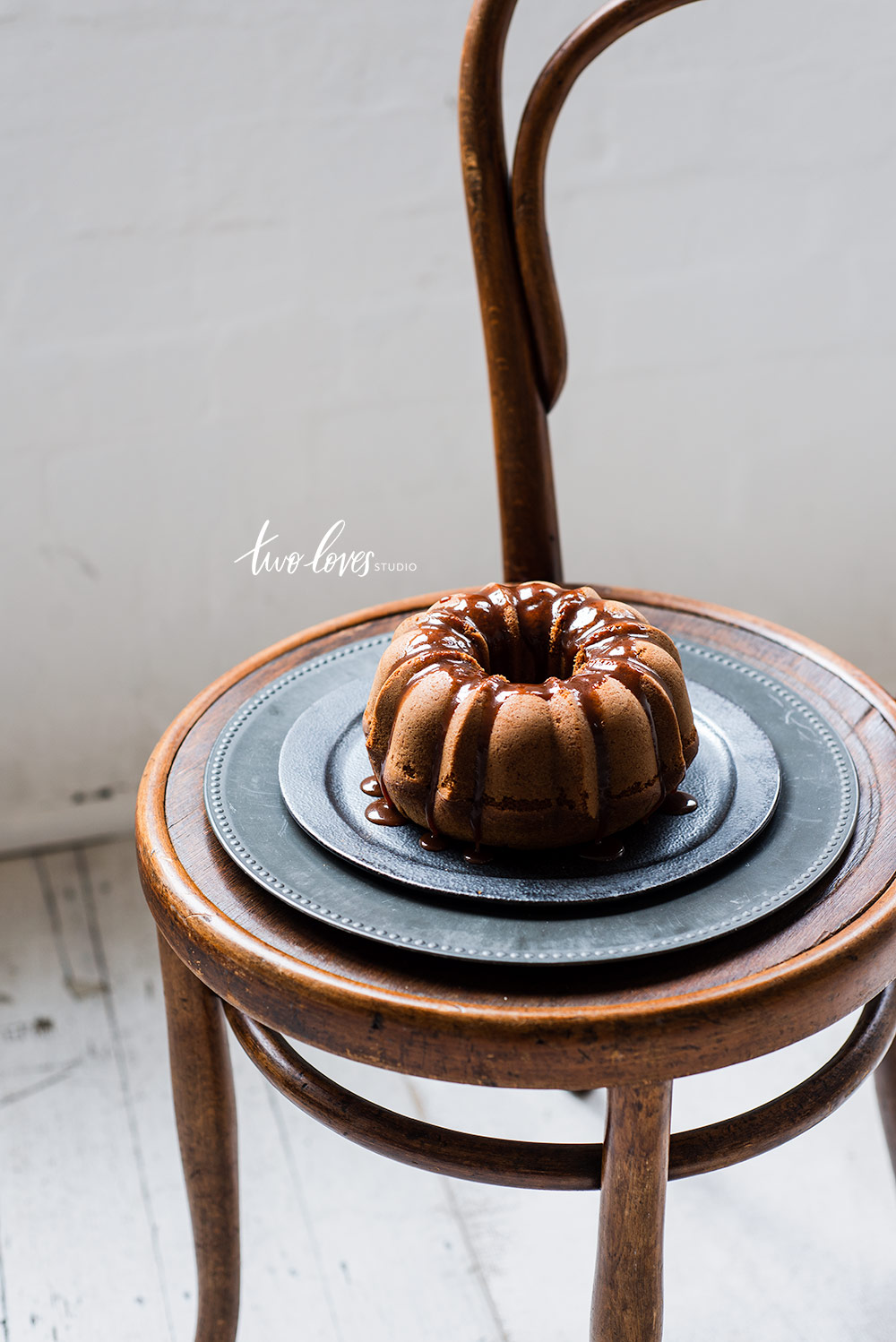 A bunt cake on top of a chair and a dark plate.