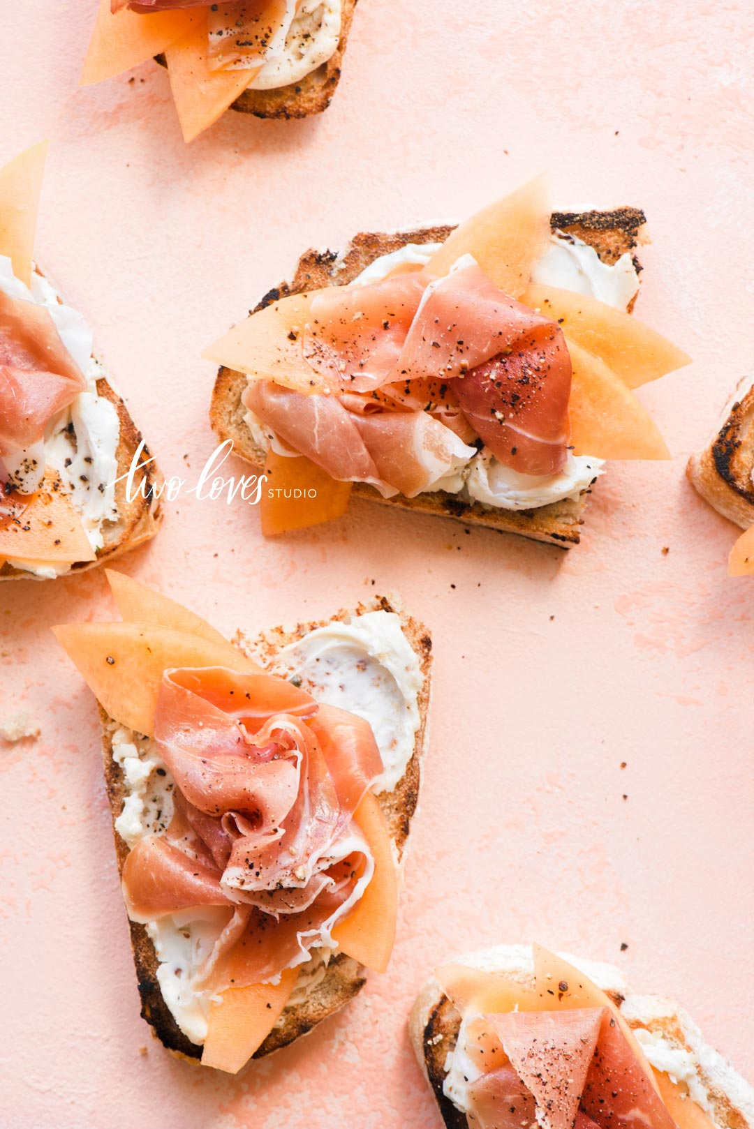 Pink backdrop on slices of toasted slices of bread with cream cheese and smoked salmon.