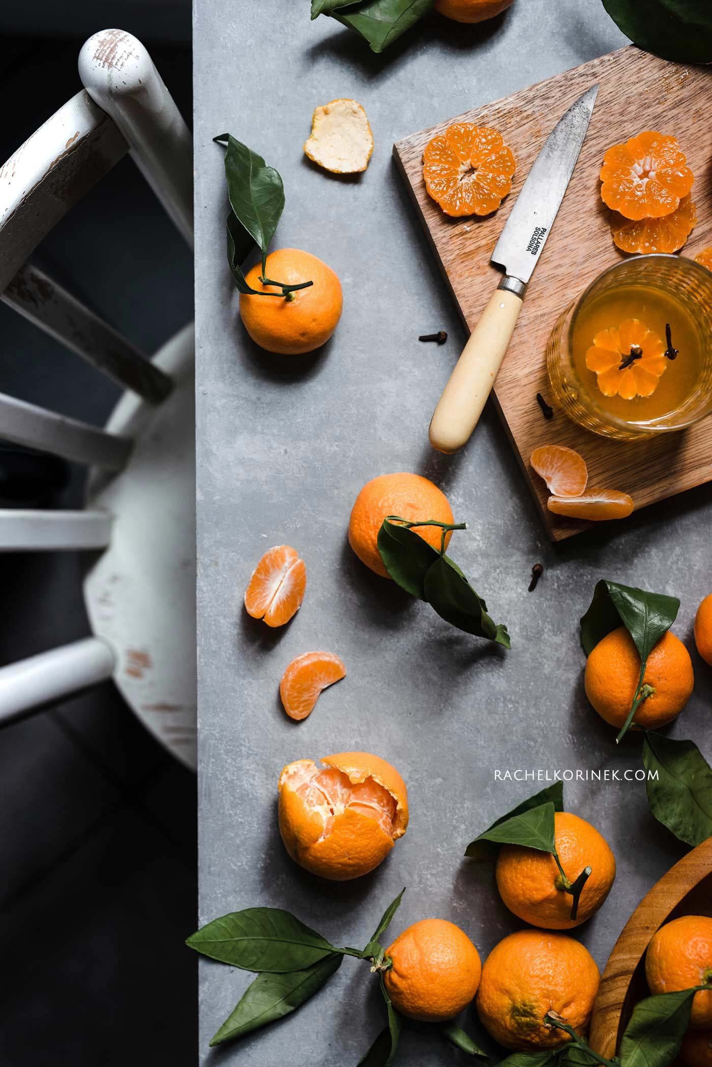 A table full of clementines, some cut up and a knife on the table.