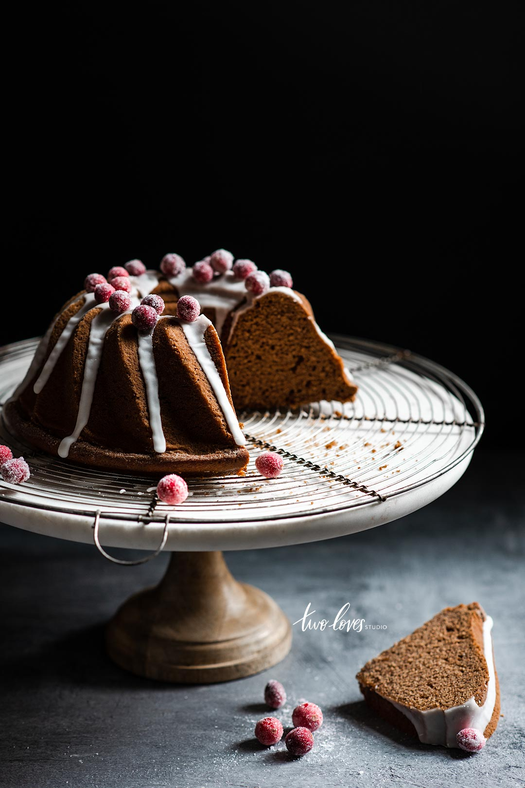 Bundt cake with a white frosting and frosted berries on a cake stand a wire cooling rack.