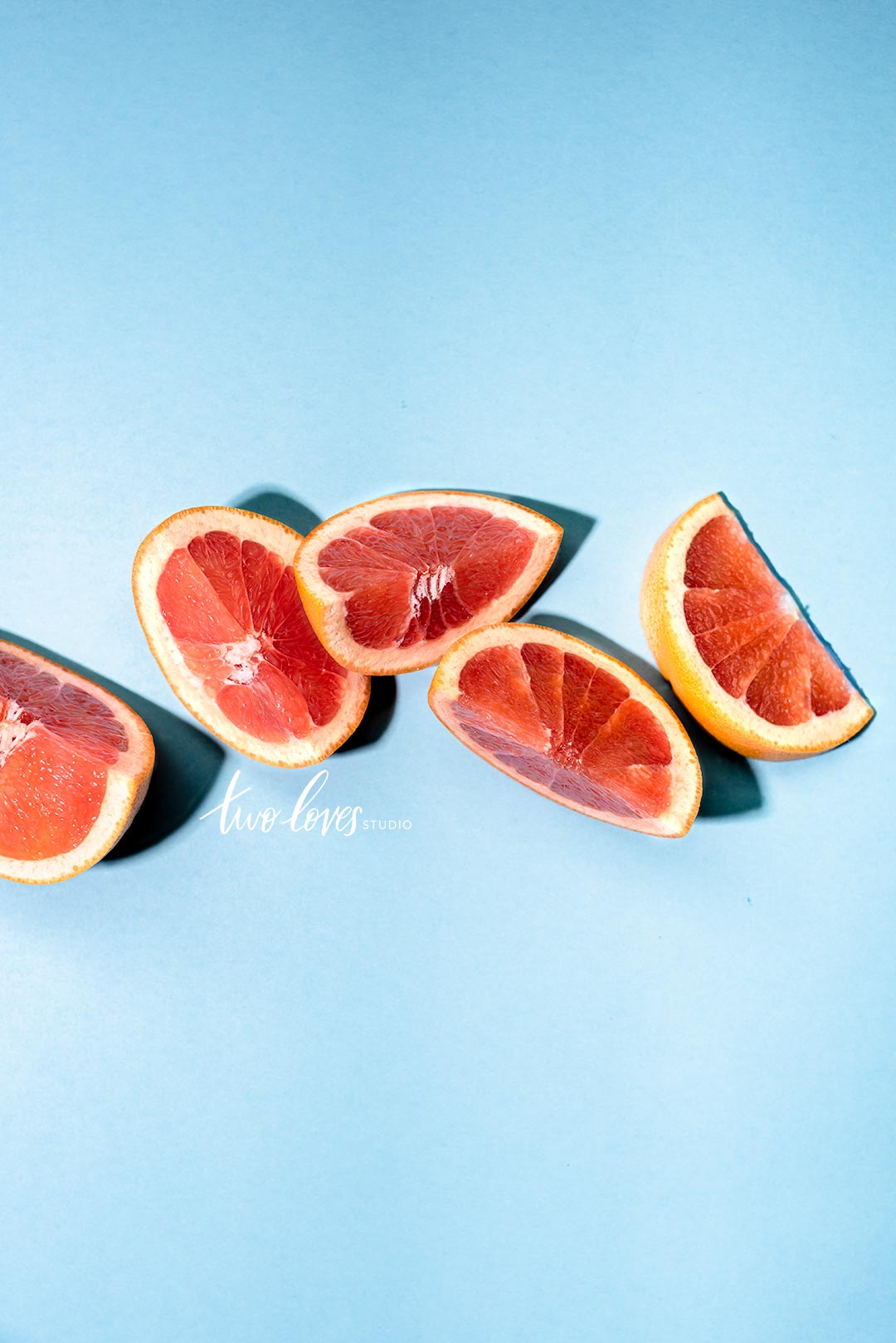 Oranges slices placed in an arrangement on a blue background.