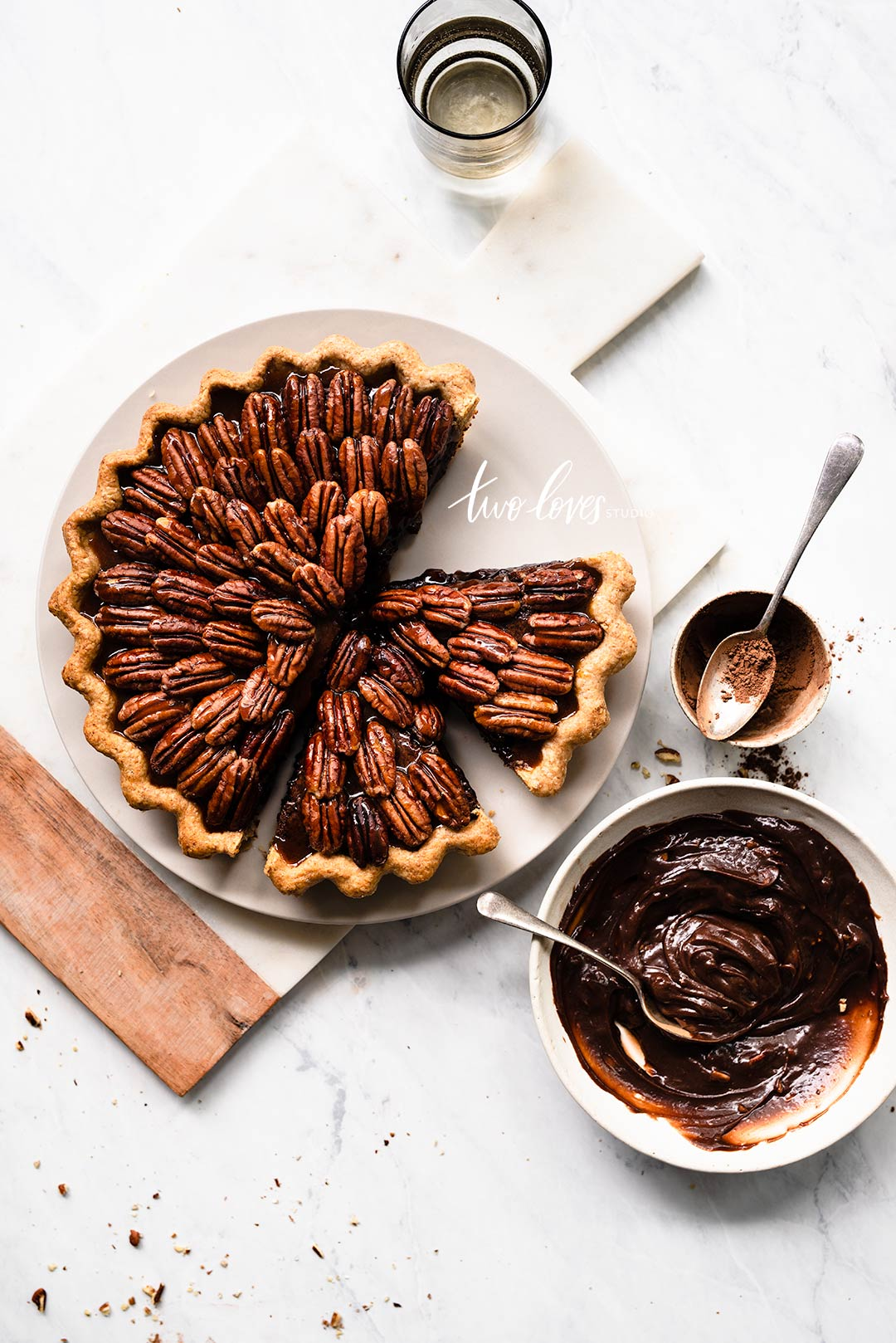 A pecan pie cut into slices on a white plate