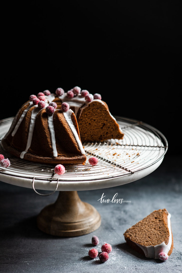 Bundt cake on a cake stand with a wire cooling rack. White frosting and frosted berries.