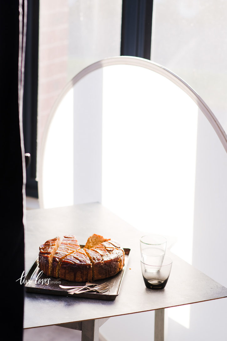An upside down banana cake with a diffuser for food photography.