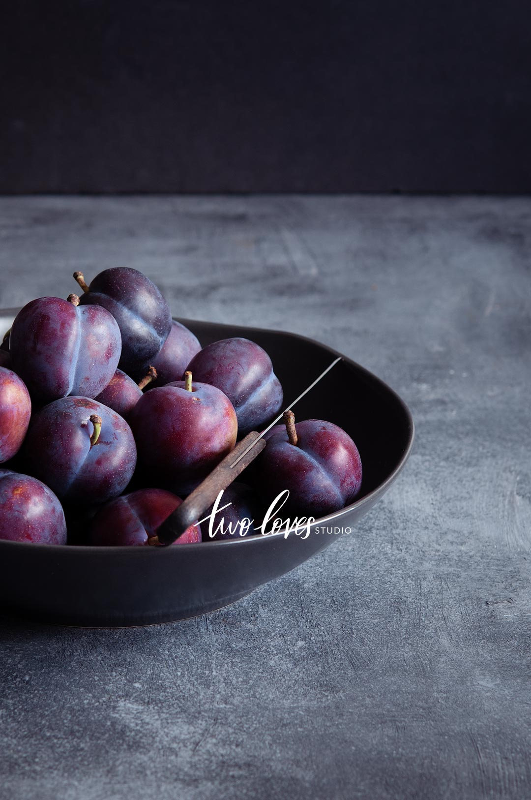 A bowl of plums in a dark lighting setup.