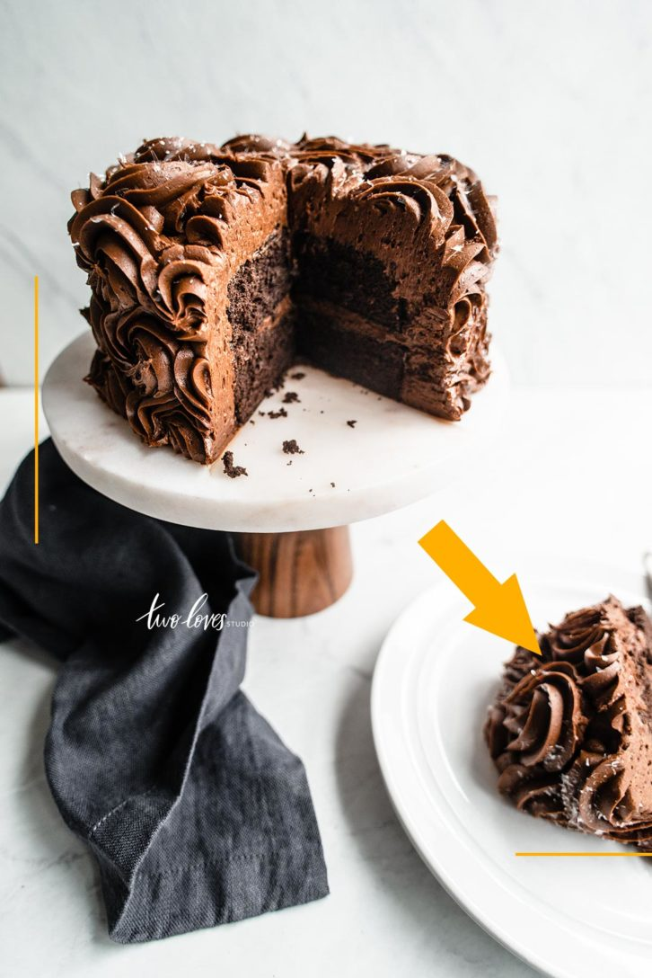 Chocolate cake on top of a cake stand with a slice cut out on a white background.