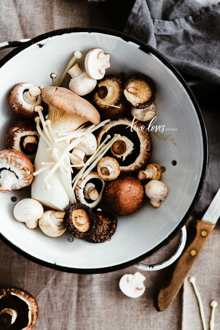 An assortment of different mushrooms in a bowl.