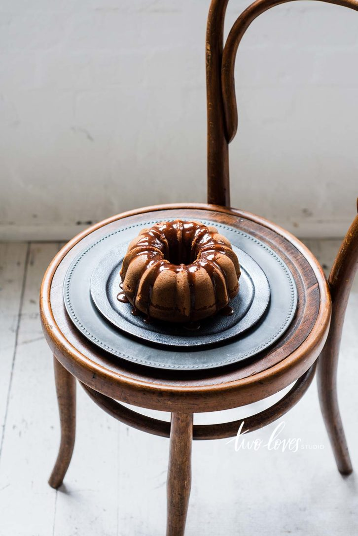 A small chair with a plate and a bundt cake on top.