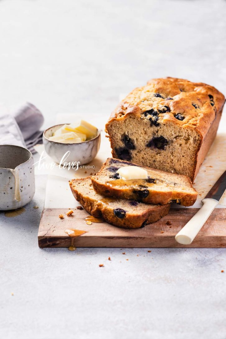 Banana cake with blueberries and a side dish of butter.