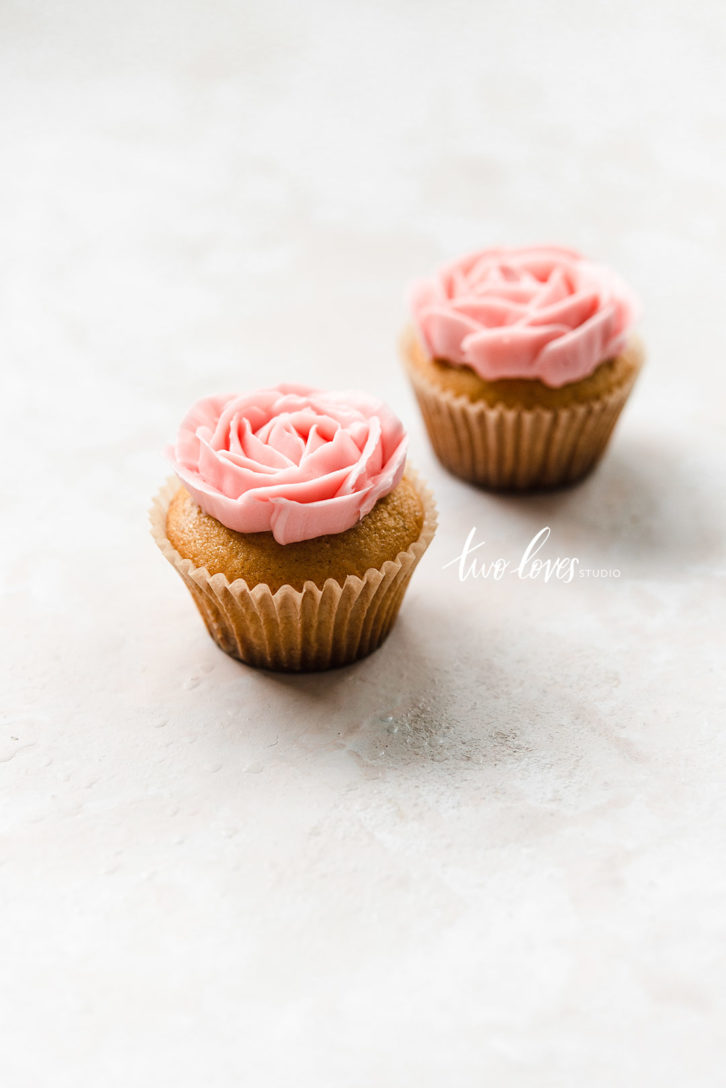 Two cupcakes with pink flowers piped on top.
