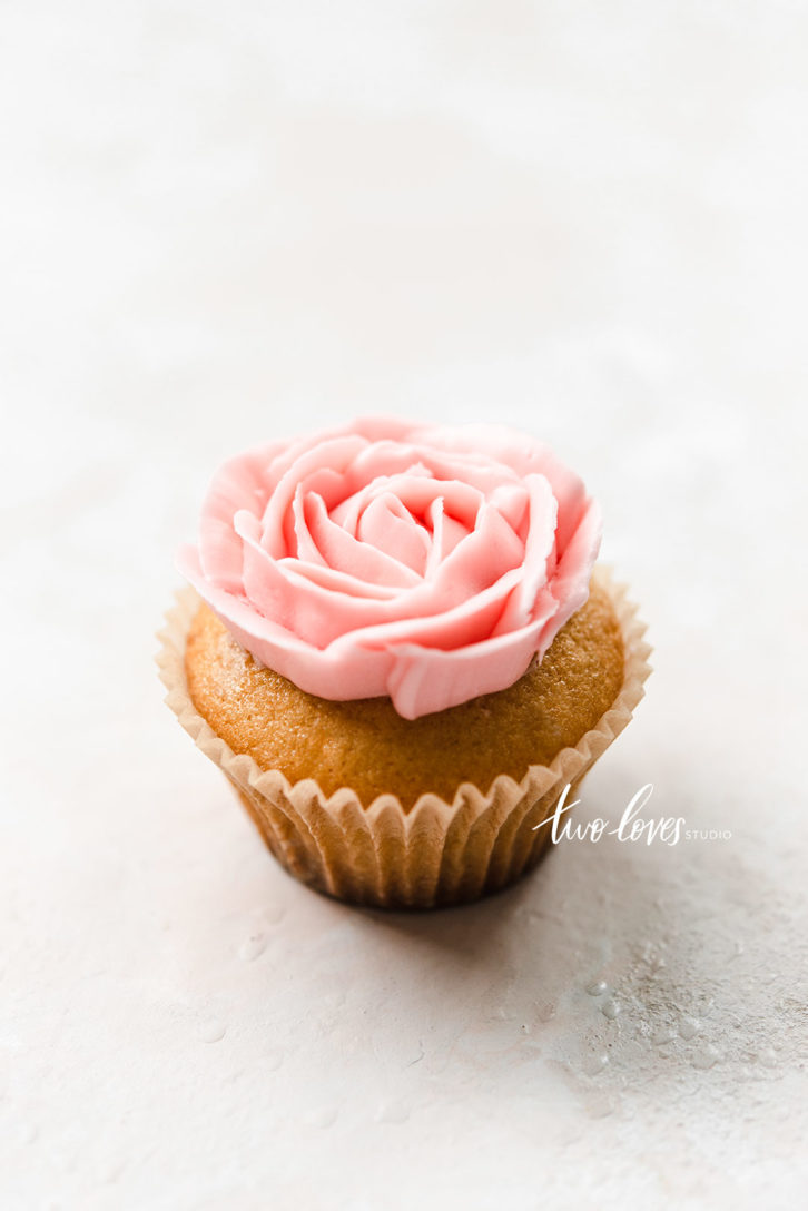 Cupcake with a pink flower piped on-top.