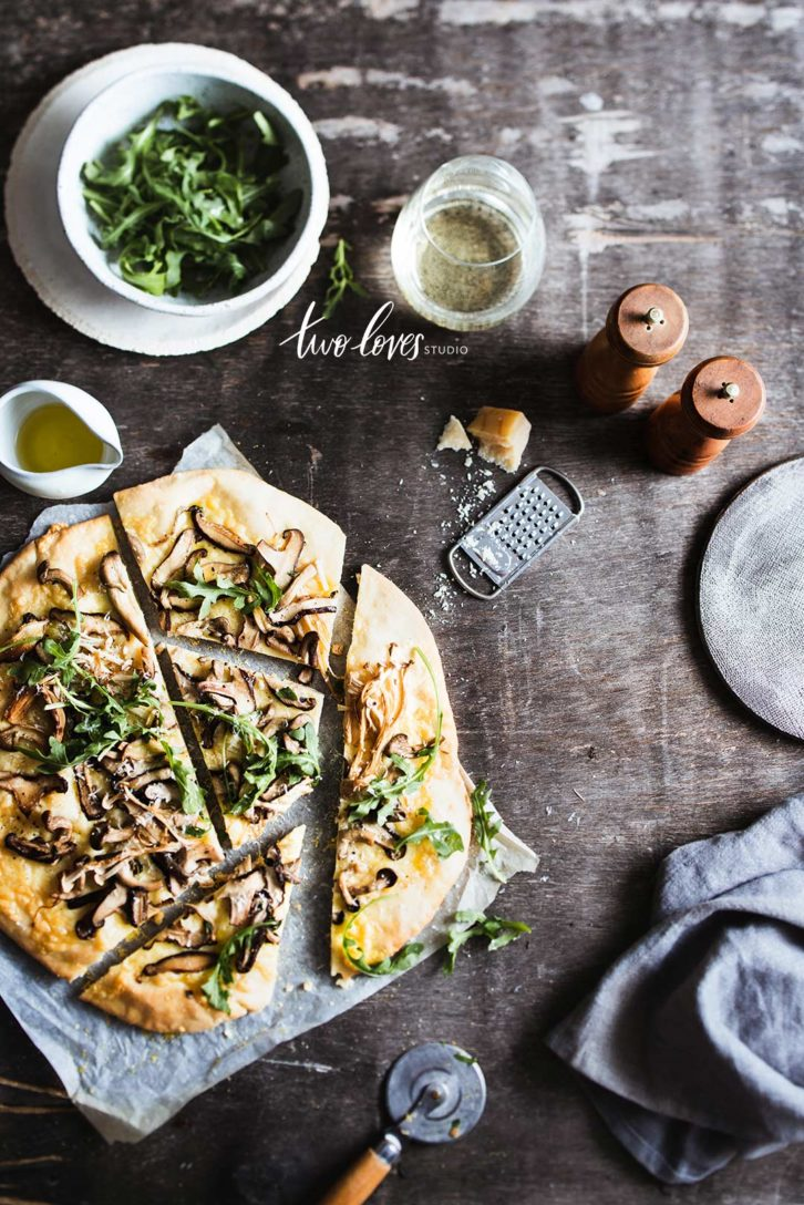 Mushroom Pizza sliced with an assortments of props.