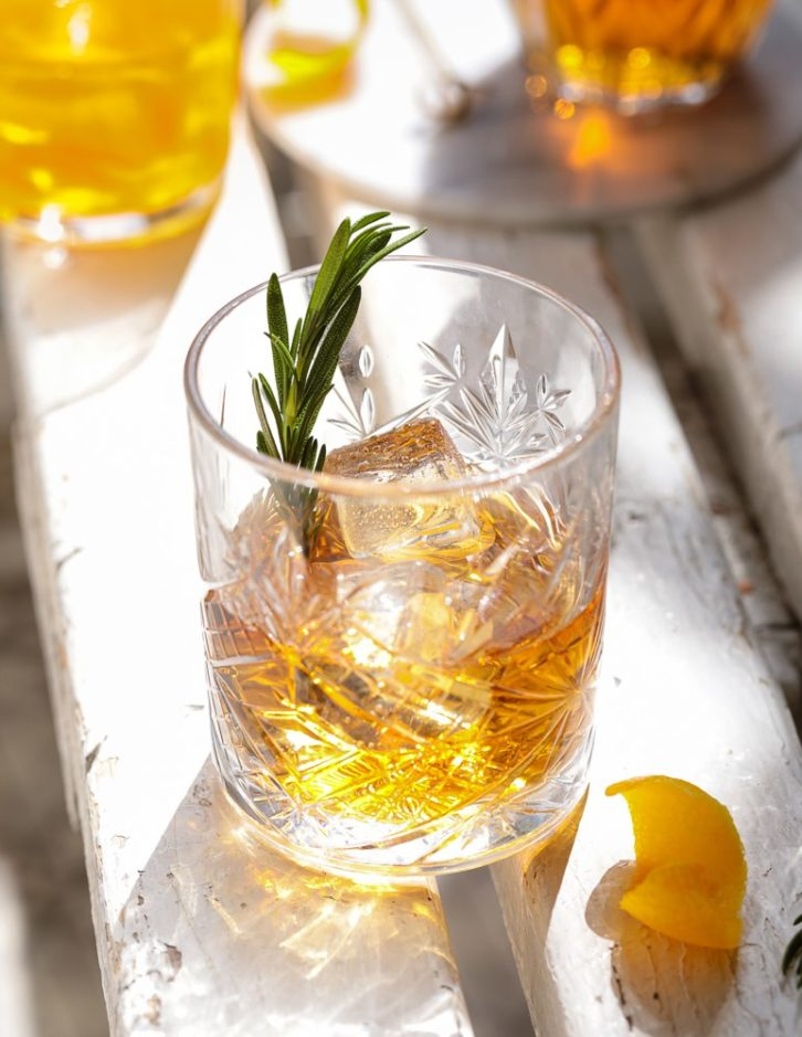 Cocktail glass with a slice of lemon and a spring of rosemary