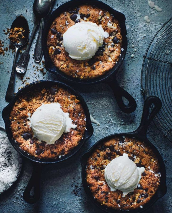 3 desserts in iron cast pans with ice cream on top.