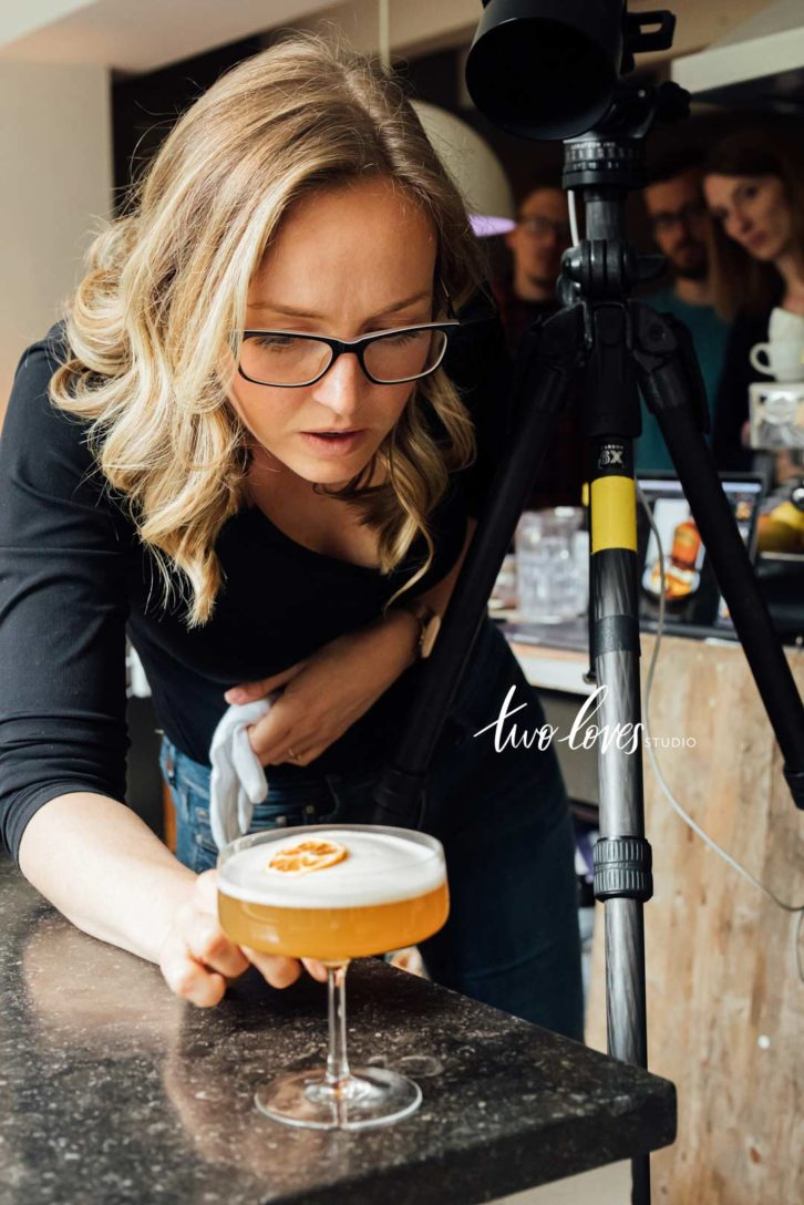Rachel Korinek adjusting a cocktail glass for a photo