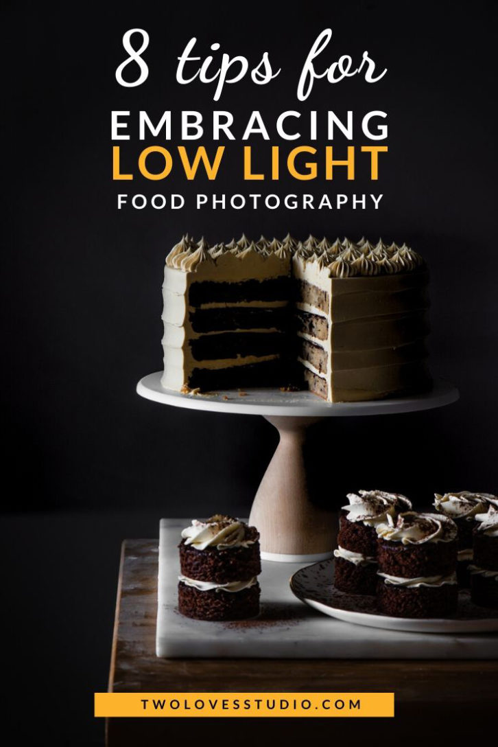 Low light food photography with cake on cake stand and mini mocha cakes surrounding it.