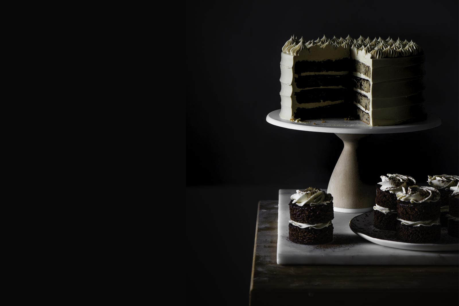 Layered banana cake on a cakes stand with devils food cupcakes surrounding it in a dark room.