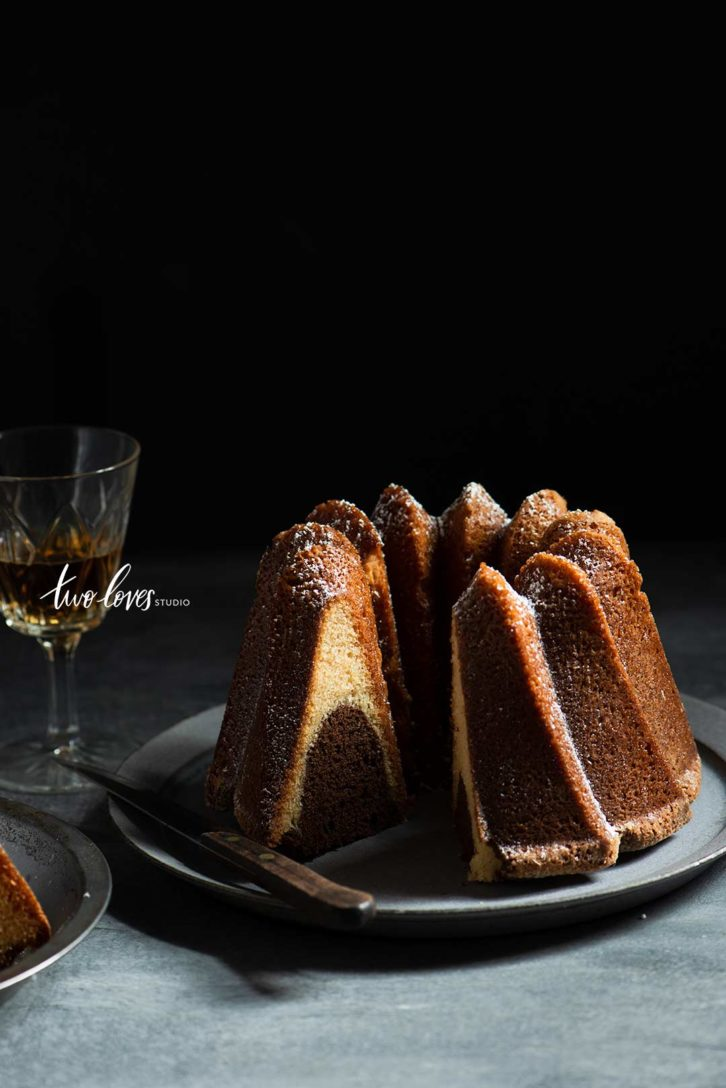 Low light food photography with bundt cake on plate and glass of brandy.
