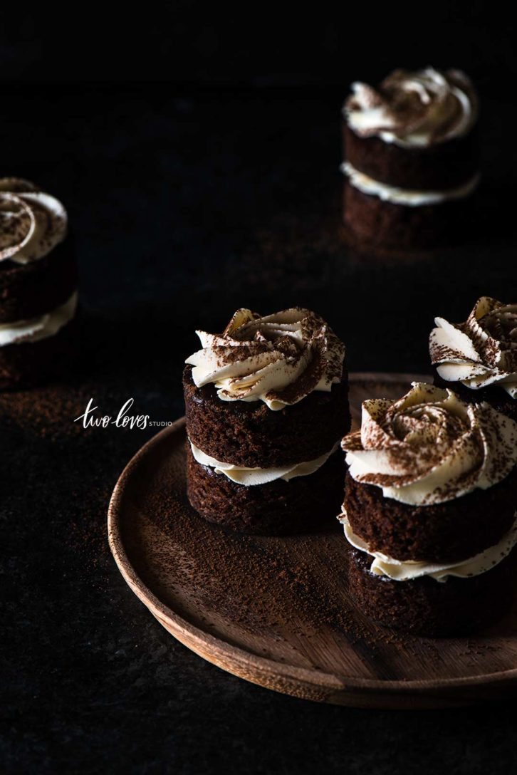 Macro shot of individual mocha cakes in low light food photography.