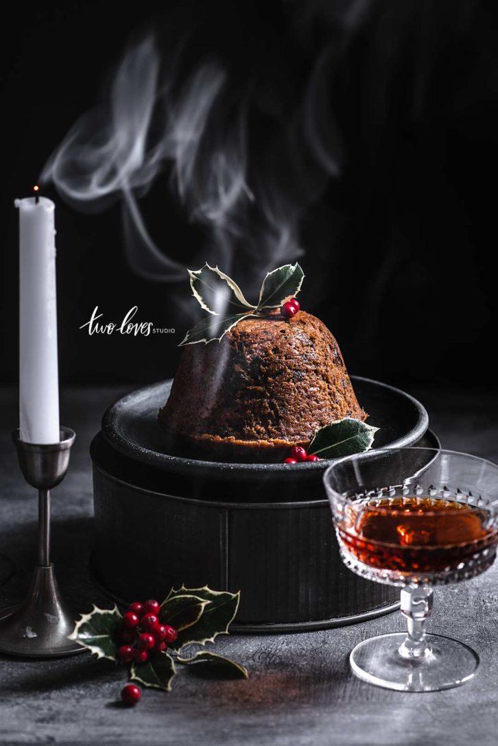 Christmas pudding food photography scene with candles and smoke.