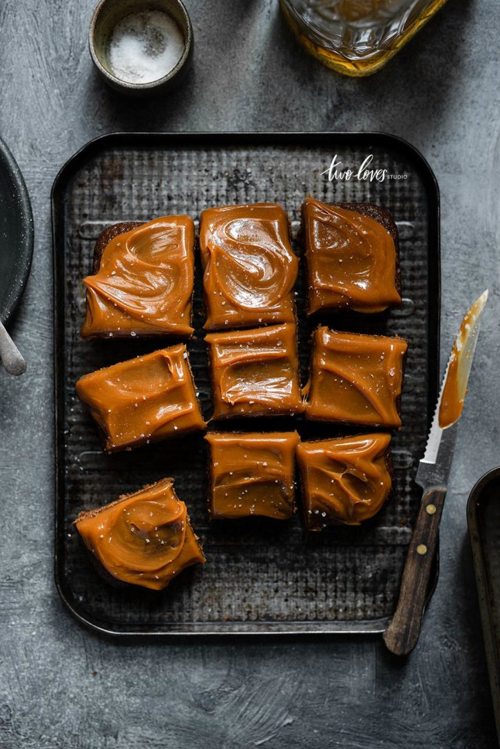 Cake cut into square pieces with caramel topping.