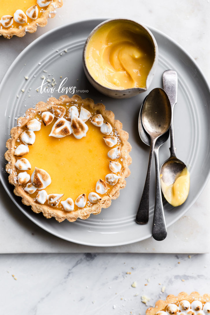 Lemon meringue tart wreaths on a grey plate with silver spoons and a side pot of lemon tart filling.