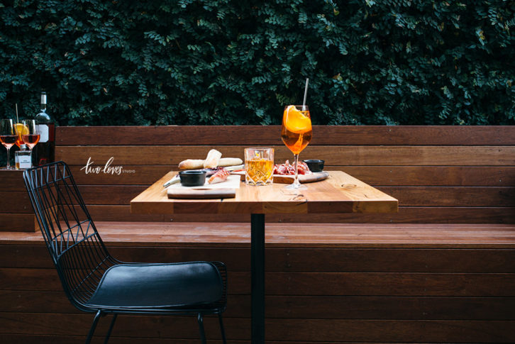 Appetizers and drinks on a table in a patio outdoor setting.
