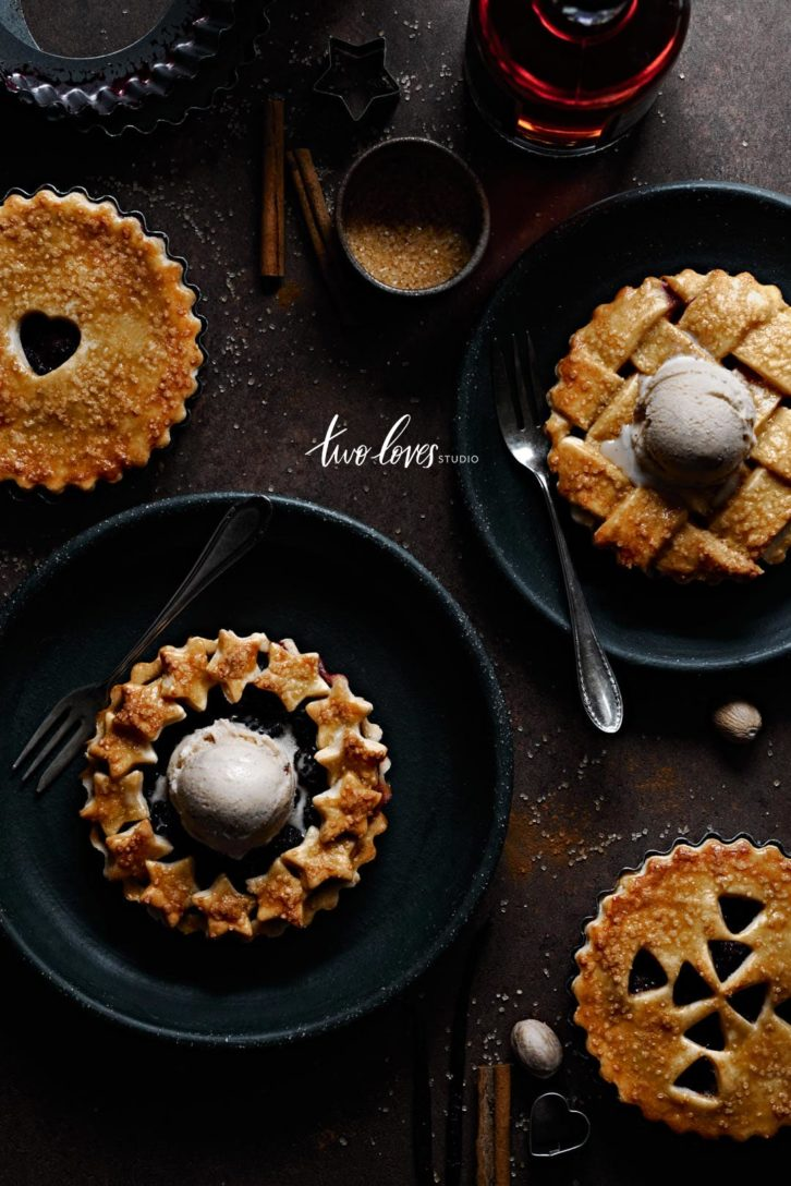 Four mini berry pies with ice-cream. All different details on top. Star wreath, classic criss cross along with heart cutouts and arrows.
