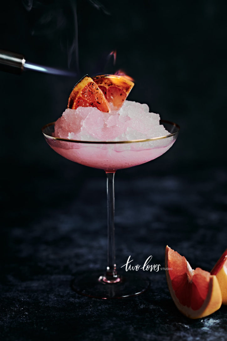 Pink icy cocktail with charred grapefruit slices.