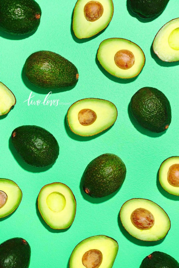 Flat-lay of avocados, some cut open others whole.