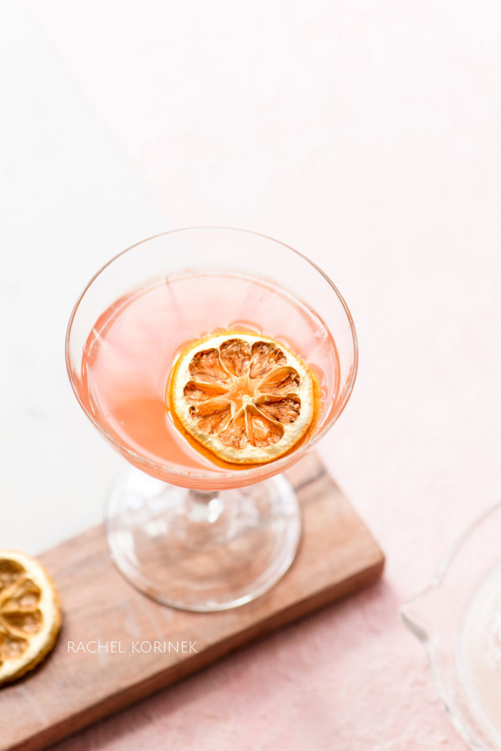 Pink cocktail in a classic cocktail glass, with a decorative dried lemon slice.