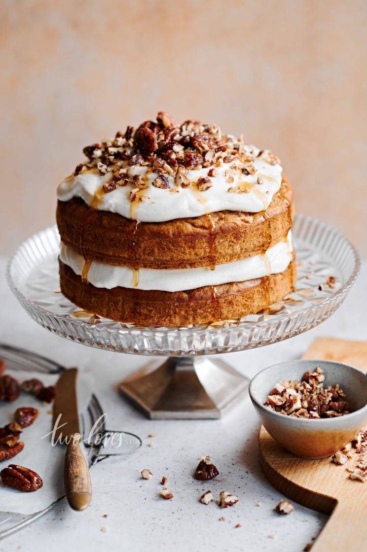 Layered carrot cake with cream cheese icing and maple syrup drizzle. Topped with chopped pecans.