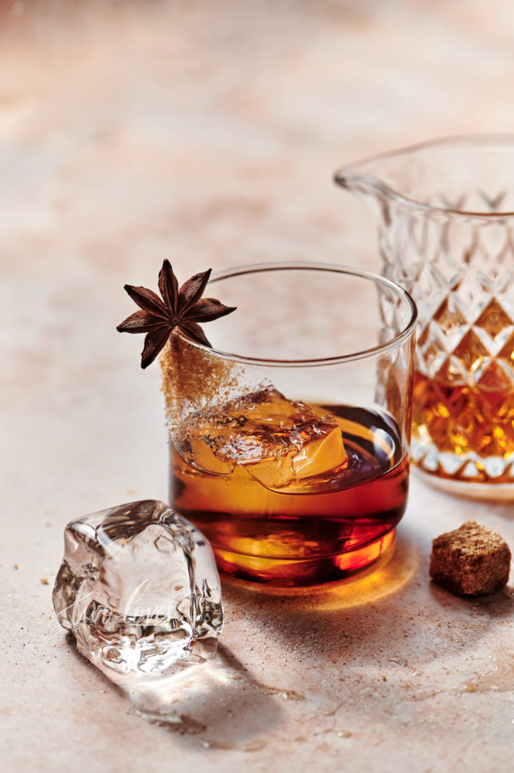 A whiskey glass filled with rich whiskey, a clear ice cube and garnished with raw sugar and a star anise.