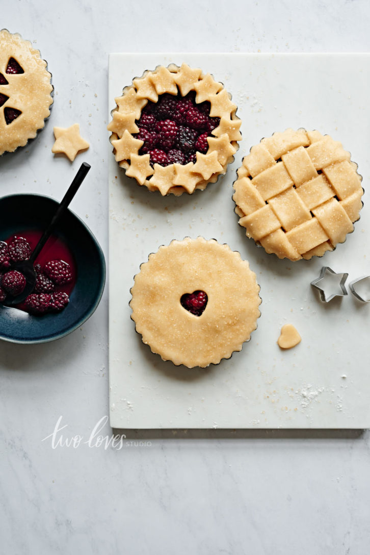 Four mini blackberry pies on a white background. Each pie has a unique lattice work design.