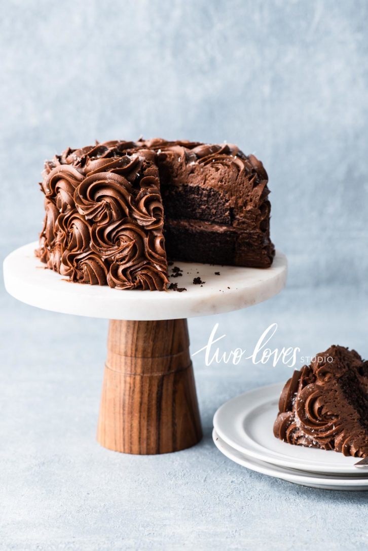 A chocolate swirl cake with a slice cut out on a plate.