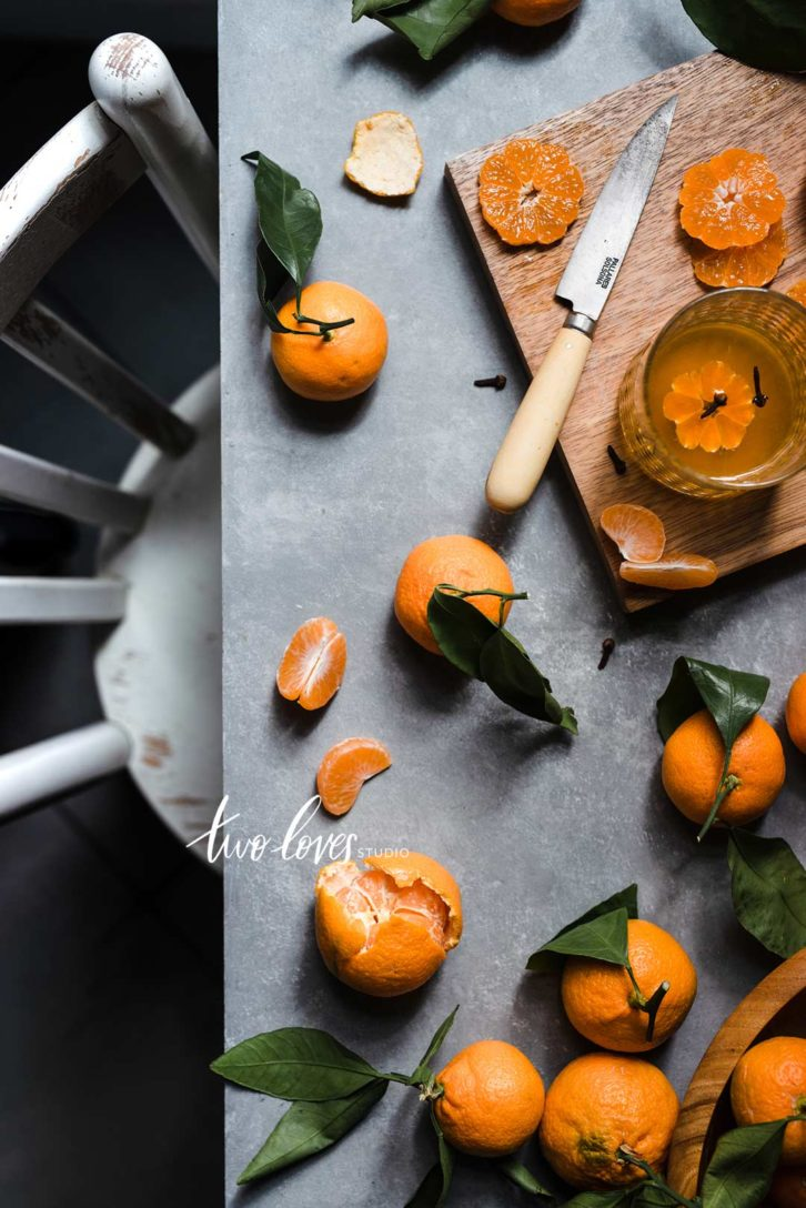 A flatlay of clementines with a chair and table.