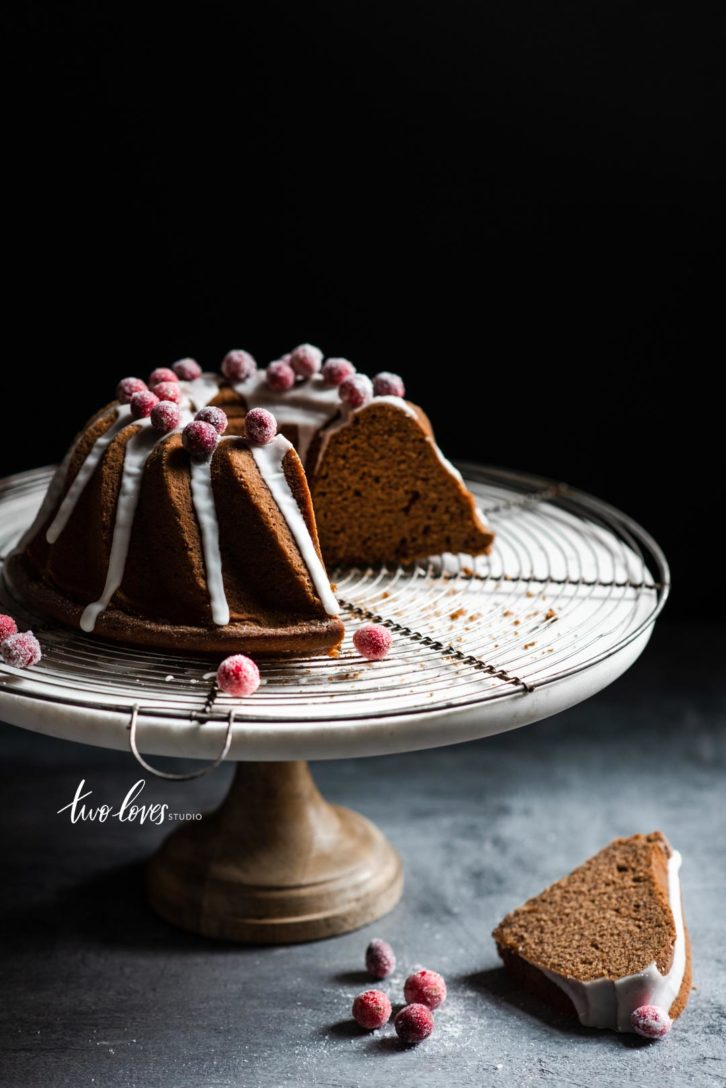 A gingerbread bundt cake cut into slices with icing drizzle and sugared cranberries on a cake stand.