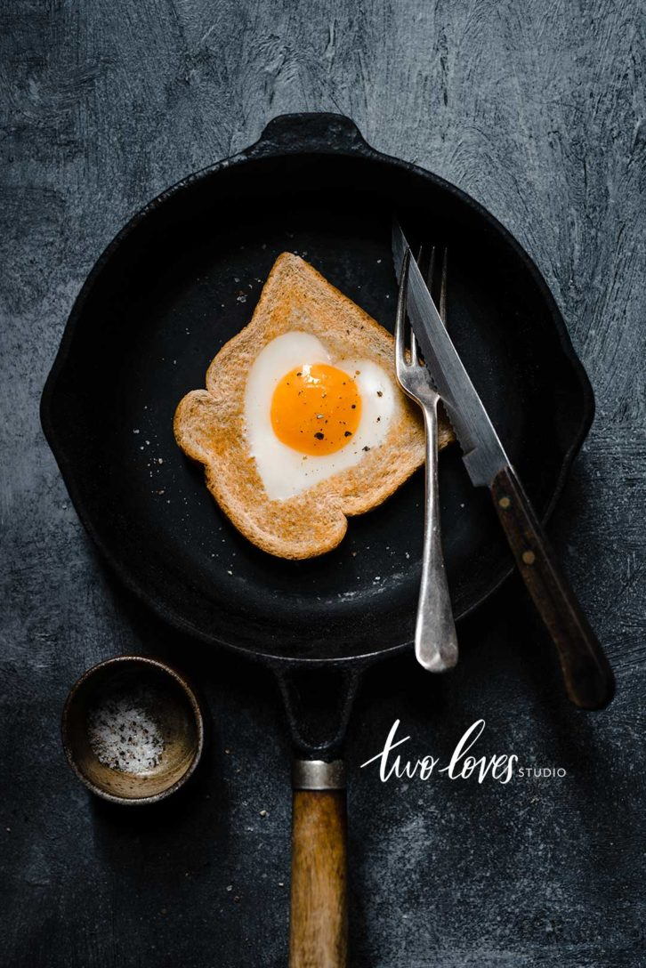 A slice of bread with a heart shaped egg in the middle. Sitting in a black skillet.