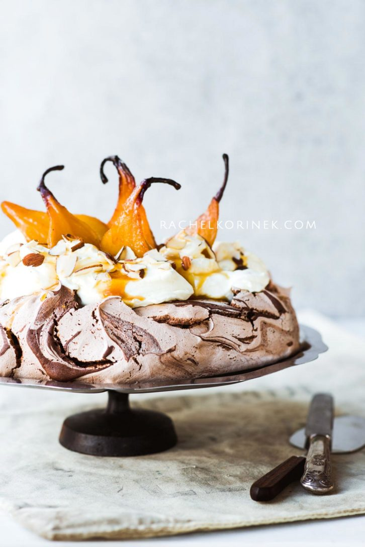 Chocolate swirl pavlova with poached pears on top.