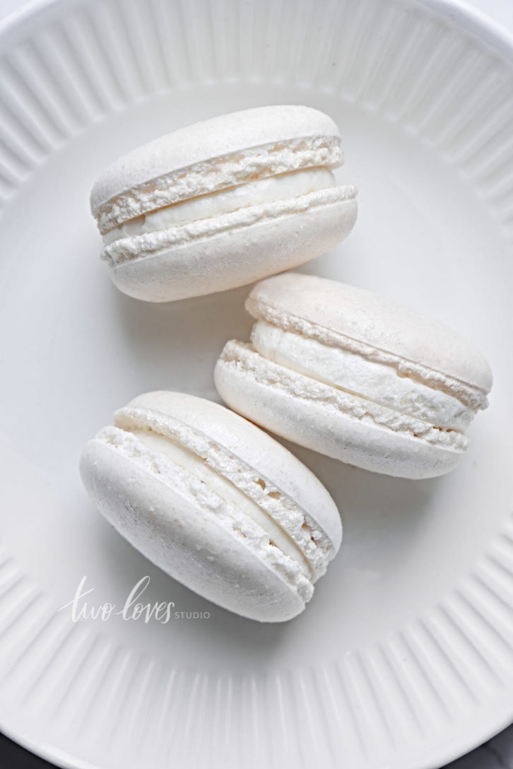 Three white macarons on a plate.