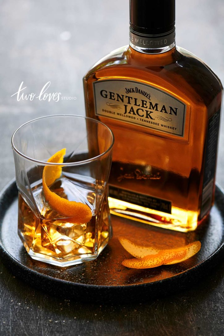 A glass of whiskey with an orange peel garnish sitting next to a bottle of Gentleman Jack.