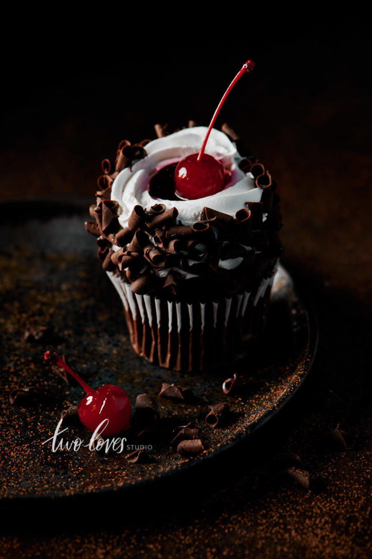 Black forest cupcake with a cherry on top. Sitting on a brown plate, with whipped cream and chocolate curls.