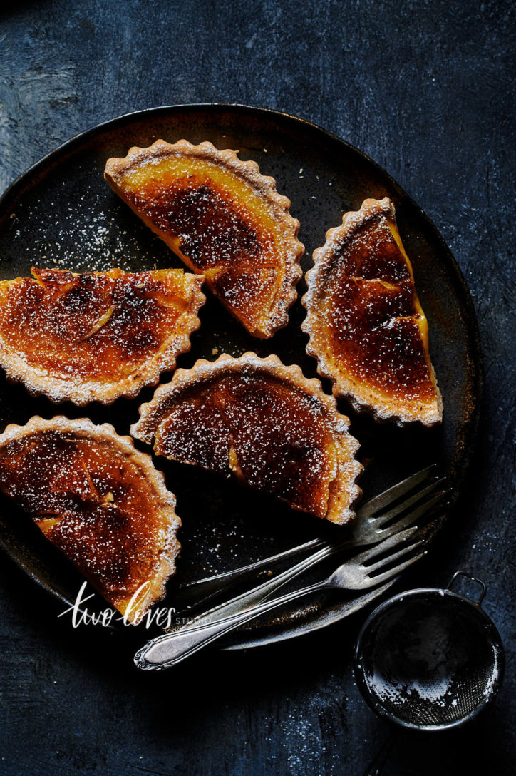lemon tarts that have been bruleed on a dark plate with three forks.