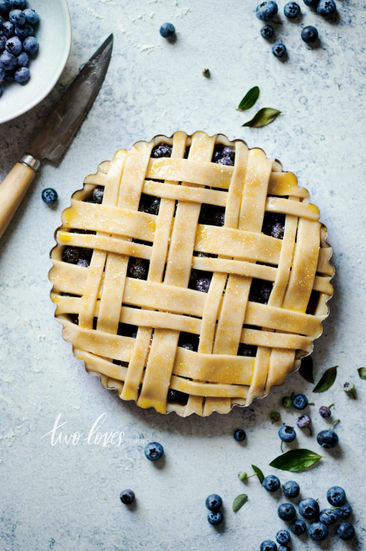 An uncooked blueberry pie with a double lattice work.